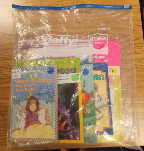 This shows the larger Hefty book bag (2.5 gallon) with a smaller Ziploc baggie (1 gallon) inside. The larger book bag stays at school, and any books students want to take home at night go into the small Zip-loc baggie.